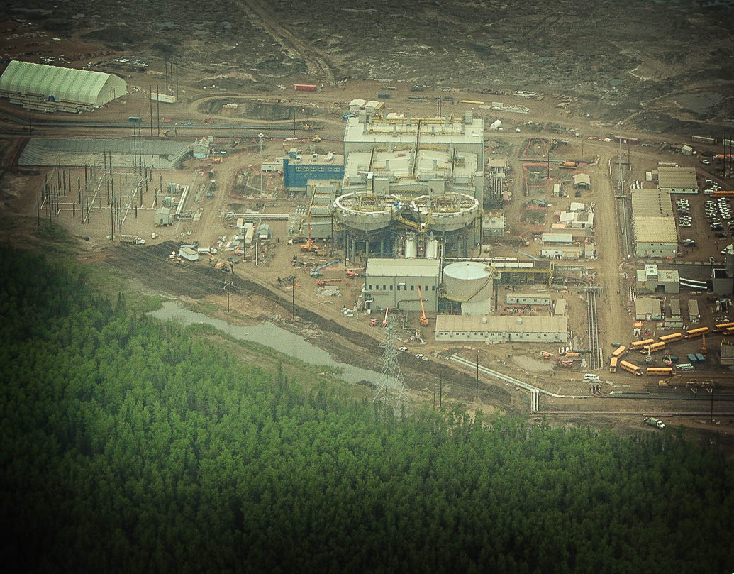 A bird's-eye view of a Fort McMurray industrial plant, next to a dense boreal forest.